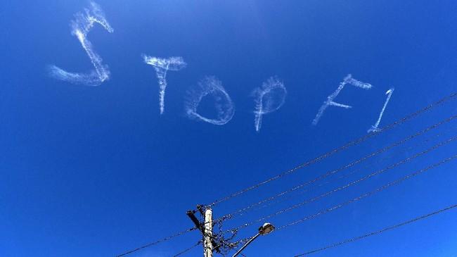 Langit Sydney berhias tulisan 'Stop F1' pada Rabu (11/3) terkait permintaan menunda balapan GP F1 Australia 2020 karena isu corona. Balapan pun resmi dibatalkan menyusul salah seorang staf tim F1 dinyatakan positif terjangkit virus yang menyerang sistem pernapasan itu. (Photo by DAVID GRAY / AFP)