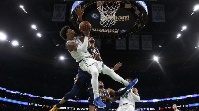 Marcus Smart dari Boston Celtic berupaya melewati adangan pemain Utah Jazz, Rudy Gobert, dalam lanjutan laga NBA. Gobert belakangan diketahui menjadi salah satu atlet yang terinfeksi virus corona. (AP Photo/Winslow Townson)