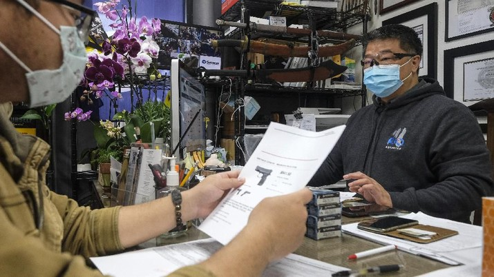 David Liu, right, owner of a gun store, takes an order from a customer in Arcadia, Calif., Sunday, March 15, 2020. Coronavirus concerns have led to consumer panic buying of grocery staples and now gun stores are seeing a run on weapons and ammunition as panic intensifies. (AP Photo/Ringo H.W. Chiu)