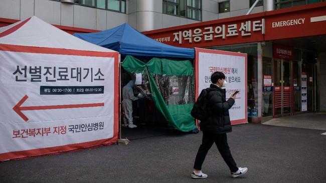 Hingga Senin (16/3) tengah malam, bilik telepon telah menerima hampir 300 ribu orang. Sebelumnya, Korea Selatan juga memperkenalkan metode drive-through agar warga tak perlu turun dari mobil untuk menjalani tes.(Photo by Ed JONES / AFP)
