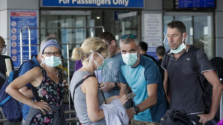 Foreigners wearing protective masks prepare to enter the departure area of Manila's International Airport, Philippines on Wednesday, March 18, 2020. The Philippine government lifted a 72-hour deadline for thousands of foreign travelers to leave the country's main northern region which has been placed under quarantine due to the growing number of coronavirus infections, officials said. For most people, the new coronavirus causes only mild or moderate symptoms. For some, it can cause more severe illness, especially in older adults and people with existing health problems. (AP Photo/Joeal Calupitan)