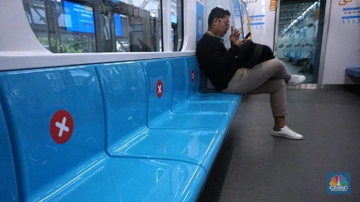 Pengunjung MRT duduk di bangku yang telah diberi stiker panduan jarak