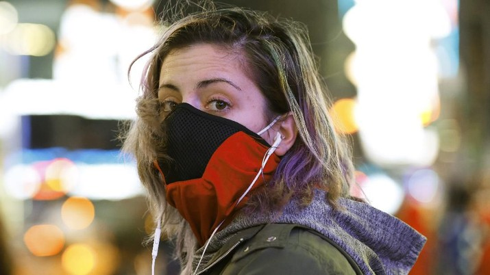 Brooklyn resident and waitress Casey Stewart peers out from a ski mask she adapted to protect herself from coronavirus after riding the subway to Times Square, Thursday, March 12, 2020, in New York to see for herself the virus outbreak's effect on the city. She is also wearing a protective mask beneath the ski mask. Stewart, who works at two restaurants, said she's definitely noticed a drop in the number of customers. She's also concerned because at least one of the places she works may have to close for at least a week or possibly longer. (AP Photo/Kathy Willens)