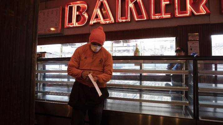 An employee of Junior's Restaurant picks up a paycheck, Thursday, March 19, 2020 in the Brooklyn borough of New York. The restaurant company, which has closed its four locations due to the coronavirus, has laid off 650 of 850 employees. (AP Photo/Mark Lennihan)
