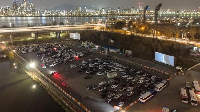 Akan tetapi, di bioskop kendara milik Park Dong-ju, para penikmat film dapat menikmati film dari kursi mobil nyaman mereka, terparkir persis di depan layar besar yang terpampang beratapkan langit terbuka. (Photo by Ed JONES / AFP)