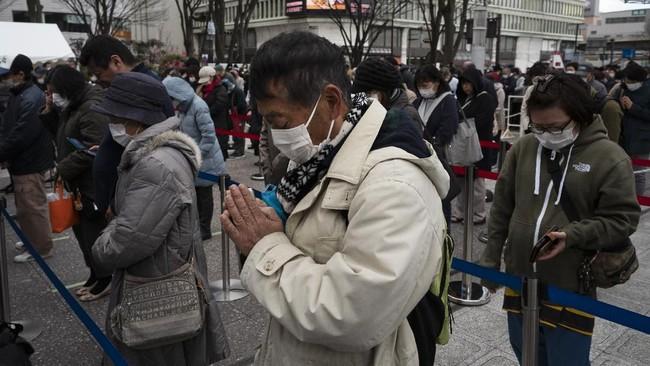 Doa bersama dilakukan para pengunjung yang ingin melihat api Olimpiade. Di tengah wabah virus corona, makna ritual menjadi kian sakral.(AP Photo/Jae C. Hong)