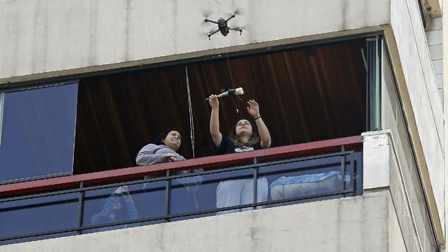 Seorang perempuan di balkonnya mengambil bunga yang diantarkan lewat drone. Saat ini masyarakat Libanon telah lebih dari satu pekan menjalani masa karantina di rumah. (Photo by JOSEPH EID / AFP)