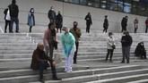 Seorang perawat memeriksa seorang pria yang pingsan saat menanti tes corona di Marseille. Bagi sebagian orang, virus ini hanya menyebabkan gejala ringan seperti batuk-batuk, tapi bagi yang lainnya bisa menyebabkan sakit parah hingga sesak napas. (AP Photo/Daniel Cole)