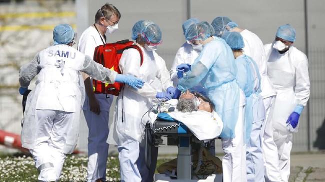 Seorang pasien Covid-19 dievakuasi dari rumah sakit umum di Mulhouse, Perancis, bagian timur. Saat ini wilayah timur Perancis menjadi pusat wabah dengan jumlah kematian tertinggi ketiga di Eropa setelah Italia dan Spanyol. (AP Photo/Jean-Francois Badias)