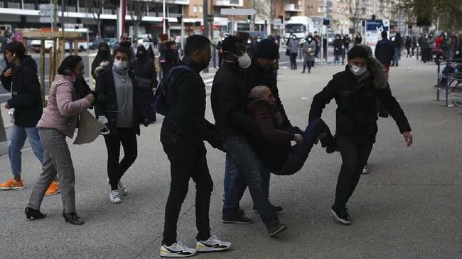 Seorang pria yang pingsan saat mengantre untuk tes corona dibawa oleh petugas. Saat ini pandemi corona telah menyebar ke 180 negara, dengan Prancis masuk ke dalam 10 negara jumlah terinfeksi terbanyak yaitu lebih dari 19 ribu orang. (AP Photo/Daniel Cole)