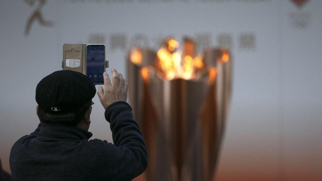 Tanpa pawai obor bukan berarti tak ada masyarakat yang ingin mengabadikan momen spesial khas menyambut Olimpiade. (AP Photo/Jae C. Hong)