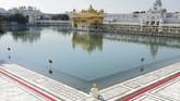 Seorang pemeluk keyakinan Sikh menyampaikan ungkapan syukurnya di Kuil Kuning, India. Saat ini India juga sedang menerapkan kebijakan pembatasan berpergian hampir di seluruh negeri. (NARINDER NANU / AFP)