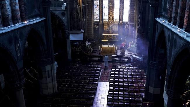 Pada akhir pekan lalu, seorang pendeta mengadakan kebaktian di ruang gereja yang kosong di Saint-Antoine. Ibadah itu kemudian ditayangkan secara langsung (live-stream) kepada para jemaat. (Kenzo TRIBOUILLARD/AFP)