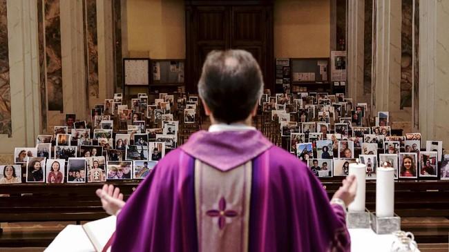 Don Giuseppe Corbari, pastur dari Gereja Robbiano, mengadakan misa pada Minggu lalu sembari menatap foto-foto selfie dari jemaatnnya. (Piero CRUCIATTI / AFP)