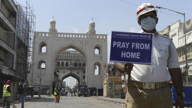 Sementara di India, seorang polisi lalu lintas memegang tanda ajakan bagi masyarakat memanjatkan doa dari rumah saja. (NOAH SEELAM / AFP)