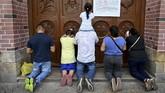 Di Kolombia, orang-orang memanjatkan doa di depan pintu gereja Basilica Yang Maha Penyembuh, berharap wabah corona segera mereda. (Luis ROBAYO / AFP)