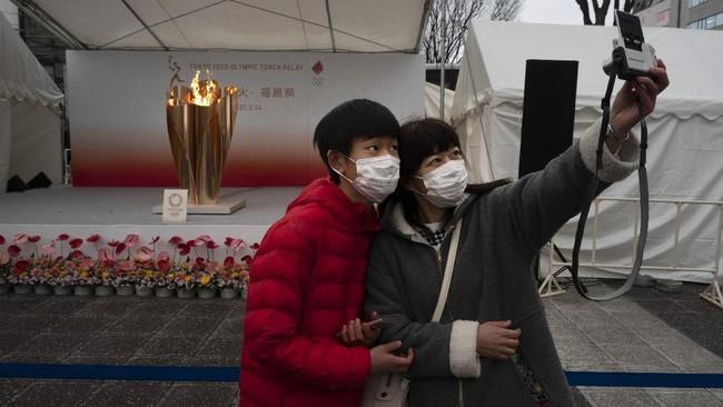 Antusiasme masyarakat menyambut api Olimpiade tetap terlihat. Swafoto menjadi ciri khas kekinian untuk mengabadikan sebuah momen penting. (AP Photo/Jae C. Hong)