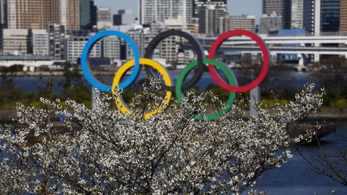 The Olympic rings floating on a barge are seen behind cherry blossoms Wednesday, March 25, 2020, in the Odaiba section of Tokyo. Not even the Summer Olympics could withstand the force of the coronavirus. After weeks of hedging, the IOC took the unprecedented step of postponing the world's biggest sporting event, a global extravaganza that's been cemented into the calendar for more than a century. (AP Photo/Jae C. Hong)
