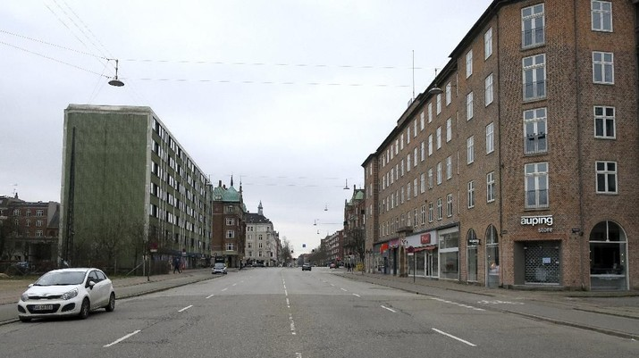 Oesterbrogade, a normally busy Copenhagen boulevard with lots of traffic is seen empty on Wednesday March 18, 2020. As of Wednesday, Denmark has banned the gathering of 10 or more people in the public room and non-food stores, restaurants and cafes will stay close. Food stores and pharmacies remain open. For most people, the new coronavirus causes only mild or moderate symptoms. For some it can cause more severe illness, especially in older adults and people with existing health problems. (AP Photos/Jan M. Olsen)
