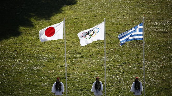 Greek Evzones guards stand next to Japan, Olympic and Greece flags, from left, during the flame lighting ceremony at the closed Ancient Olympia site, birthplace of the ancient Olympics in southern Greece, Thursday, March 12, 2020, 2020. Greek Olympic officials are holding a pared-down flame-lighting ceremony for the Tokyo Games due to concerns over the spread of the coronavirus. Both Wednesday's dress rehearsal and Thursday's lighting ceremony are closed to the public, while organizers have slashed the number of officials from the International Olympic Committee and the Tokyo Organizing Committee, as well as journalists at the flame-lighting. (AP Photo/Yorgos Karahalis)