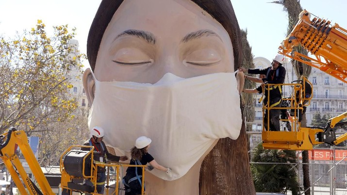 Workers place a mask on the figure of the Fallas festival in Valencia, Spain, on Wednesday, March 11, 2020. The festival planned to take place on March 13 has been canceled over the coronavirus outbreak. For most people, the new coronavirus causes only mild or moderate symptoms, such as fever and cough. For some, especially older adults and people with existing health problems, it can cause more severe illness, including pneumonia. (AP Photo/Alberto Saiz)