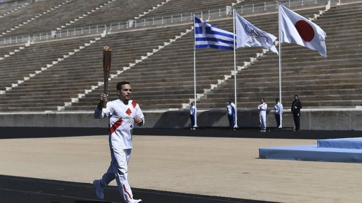 Lefteris Petrounias, Greek Olympic Champion in artistic gymnastics runs with the Olympic torch during the Olympic flame handover ceremony for the 2020 Tokyo Summer Olympics, in Athens, Thursday, March 19, 2020. The ceremony was held behind closed doors and with the presence of few members of the media because of fears over the new coronavirus. (Aris Messinis/Pool via AP)