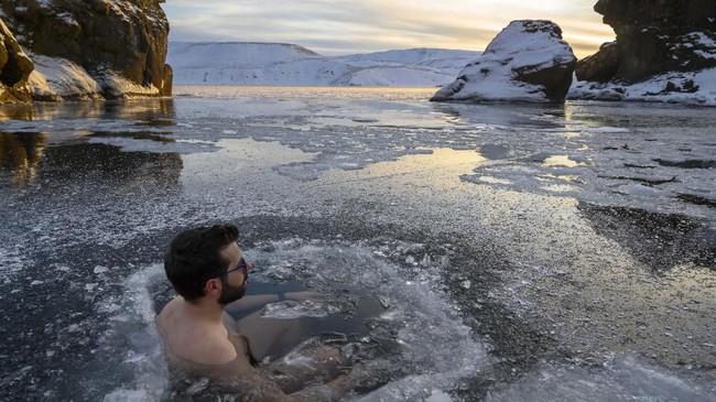 Orang-orang yang hadir dalam seminar berendam dalam es ini sudah menjalani program selama empat minggu. Menceburkan diri ke danau beku Kleifarvatn menjadi puncaknya. (Halldor KOLBEINS / AFP)