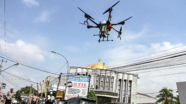 Tim gabungan Polda Riau beserta Polresta Pekanbaru mengoperasikan drone untuk menyemprotkan cairan disinfektan di kawasan pemukiman penduduk. Teknologi drone membuat penyemprotan disinfektan lebih efisien karena mampu menjangkau tempat-tempat yang sukar didatangi. (ANTARA FOTO/Rony Muharrman)