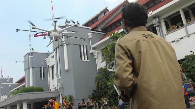 Di Surabaya, pemerintah juga menggunakan 'drone' untuk menyemprotkan larutan disinfektan di Balai Kota Surabaya. Fasilitas publik menjadi salah satu tempat yang harus dipastikan keamanannya mengingat tak semua layanan bisa digantikan dengan sistem kerja dari rumah. (ANTARA FOTO/Didik Suhartono)