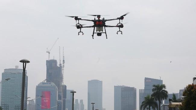 Sebuah drone menyemprotkan disinfektan dari ketinggian di kawasan Jalan Jenderal Sudirman, Jakarta, Jumat (27/3). Penyemprotan disinfektan tersebut dilakukan guna menekan penyebaran virus Corona (COVID-19). ANTARA FOTO/Reno Esnir/nz.