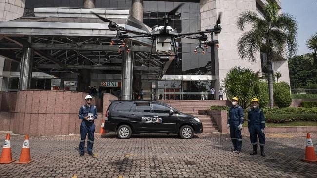 Petugas menggunakan drone (pesawat tanpa awak) untuk menyemprotkan cairan disinfektan di halaman Kantor Pusat BNI, Jakarta, Jumat (20/3). Saat ini Indonesia sedang bergelut dengan wabah corona dengan lebih dari 1000 kasus terinfeksi positif ditemukan hingga hari ini. (ANTARA FOTO/Dhemas Reviyanto).