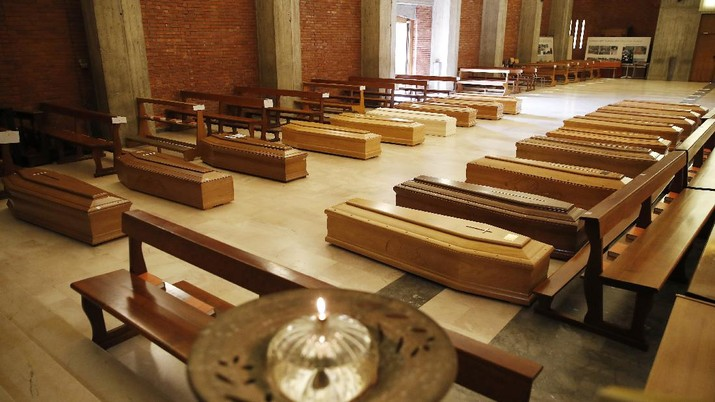 Coffins are lined up on the floor of the San Giuseppe church in Seriate, Italy, one of the regions worst hit by coronavirus, near Bergamo, waiting to be taken to a crematory, Thursday, March 26, 2020. (AP Photo/Antonio Calanni)