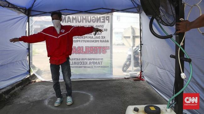 Memanfaatkan kipas angin uap air, sebuah perumahan mengharuskan pendatang masuk ke bilik sterilisasi disinfektan sebelum masuk ke perumahan warga. (CNNIndonesia/Safir Makki)