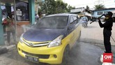 Gerbang masuk sebuah area dadakan diubah menjadi tempat penyemprotan disinfektan bagi warga yang datang dengan kendaraan roda empat. (CNNIndonesia/Safir Makki)