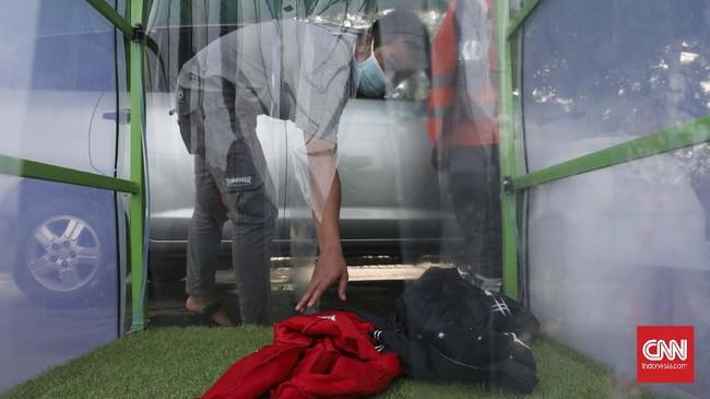 Orang yang masuk bilik disinfektan wajib melepaskan semua barang bawaannya seperti tas, jaket, helm, untuk disemprot disinfektan. (CNNIndonesia/Safir Makki)