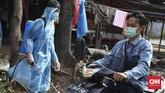 Warga, berbekal dana yang digalang secara swadaya, dituntut kreatif sekaligus berani ambil risiko. Salah satunya dengan memanfaatkan jas hujan plastik dan masker seadanya saat melakukan penyemprotan disinfektan. (CNNIndonesia/Safir Makki)