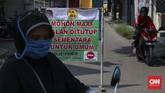 Mengenakan jas hujan plastik, masker dan tabung penyemprotan, warga permukiman di kawasan Pekayon, Bekasi, Jawa Barat, bergantian berjaga selama 24 jammelakukan penyemprotan disinfektan bagi warga dan pendatang yang datang. (CNNIndonesia/Safir Makki)