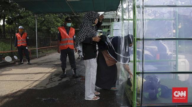 Tak perlu menunggu suntikan dana dari pemerintah, warga membuat bilik sterilisasi secara swadaya demi kesehatan. (CNNIndonesia/Safir Makki)
