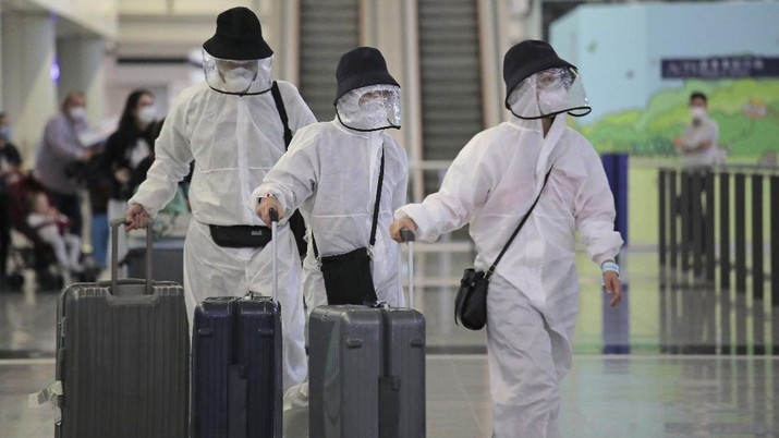 Passengers wear protective suits and face masks as they arrive at the Hong Kong airport, Monday, March 23, 2020. The new coronavirus causes mild or moderate symptoms for most people, but for some, especially older adults and people with existing health problems, it can cause more severe illness or death. (AP Photo/Kin Cheung)
