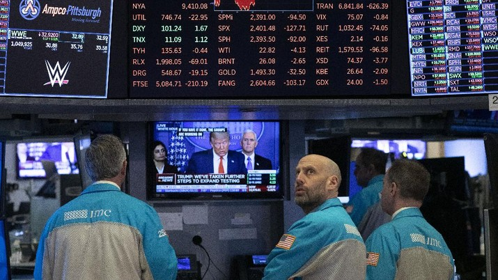 FILE - In this March 18, 2020, file photo traders at the New York Stock Exchange watch President Donald Trump's televised White House news conference in New York. When President Donald Trump speaks, financial markets gyrate and quiver in real time. (AP Photo/Mark Lennihan, File)