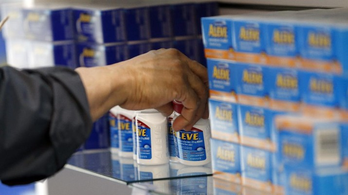 In this Wednesday, May 13, 2015, photo, an employee stocks products in the employee shop at the Bayer Pharmaceuticals facility in Whippany, N.J. Bayer now markets 170 consumer health products, 17 with annual sales topping $100 million. Those include Bayers own One A Day and Flintstones vitamins, Aleve pain reliever, Alka-Seltzer and Phillips' Colon Health, plus former Merck products including Claritin, Coppertone and Dr. Scholls foot products. (AP Photo/Julio Cortez)