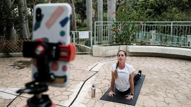 Peralatannya cukup sederhana: laptop atau telepon genggam, alas yoga, serta ruangan yang luasnya cukup untuk menjaga jarak dari orang lain agar terhindar dari penyebaran virus corona. (Photo by Anthony WALLACE / AFP)