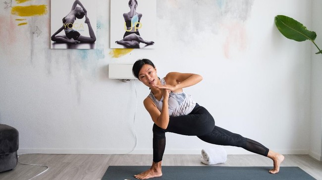 Beberapa instruktur yoga menggunakan aplikasi zoom yang membuat mereka tetap bisa menjadi pusat perhatian di tengah murid-murid yang terhubung berbarengan. Instruktur lain memberikan rekaman video serta daftar lagu penunjang di spotify. (Anthony WALLACE / AFP)
