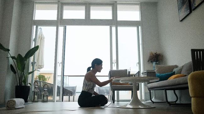 Sementara di suatu rumah lainnya di Pulau Lantau, Chaukei Ngai yang merupakan pendiri startup YogaUP menyapa murid-muridnya lewat layar laptop sebelum memulai kelas yoga online. (Photo by Anthony WALLACE / AFP)