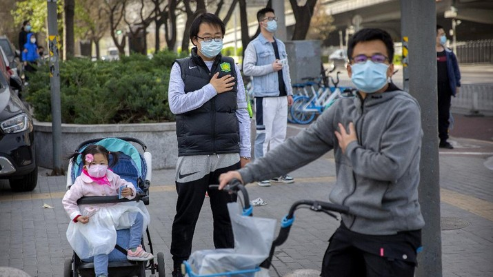 People stand along a street during a national moment of mourning for victims of the coronavirus, in Beijing, Saturday, April 4, 2020. With air raid sirens wailing and flags at half-staff, China on Saturday held a three-minute nationwide moment of reflection to honor those who have died in the coronavirus outbreak, especially