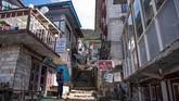 Seorang pria berdiri di jalanan kosong dekat toko-toko yang tutup di Namche Bazar. Selain menutup diri dari turis asing, Nepal juga menerapkan lockdown total di seluruh di negeri. (Photo by PRAKASH MATHEMA / AFP)
