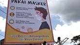 Pekerja memasang imbauan menggunakan masker di Syech Yusuf, Kendari, Sulawesi Tenggara. (ANTARA FOTO/Jojon/foc)