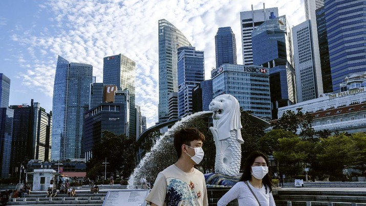 In this March 14, 2020, photo, a couple wearing face masks walk past the Merlion statue in Singapore. As the virus outbreak spreads ever further, it's becoming clear that some strategies are more likely to succeed in containing it: pro-active efforts to track down and isolate cases, access to basic, affordable public health and clear, reassuring messaging from leaders. (AP Photo/Ee Ming Toh)