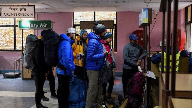 Para pendaki memeriksakan diri di bagian kedatangan di bandara Tenzing-Hillary. Bukan hanya Nepal dan Everest, seluruh tempat-tempat wisata di dunia pun dalam dua bulan terakhir ditinggal oleh para wisatawan. (Photo by Prakash MATHEMA / AFP)