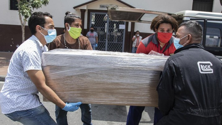 Relatives carry the remains of a loved one in a cardboard coffin for burial, as they leave a church in Guayaquil, Ecuador, Monday, April 6, 2020. Guayaquil, a normally bustling city that has become a hot spot in Latin America as the coronavirus pandemic spreads, also has untold numbers dying of unrelated diseases that can't be treated because hospitals are overwhelmed. (AP Photo/Luis Perez)